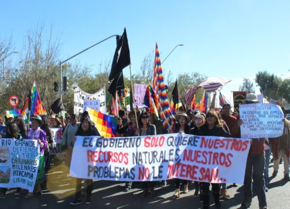 "image of protesters demonstrating against extractivism in their community. Many carry the Wiphala indigenous Andean flag. At the front of the demonstration is a banner reading ""El Gobinero solo quiere nuestros reccursos naturales, nuestros problemas no le interesan"""