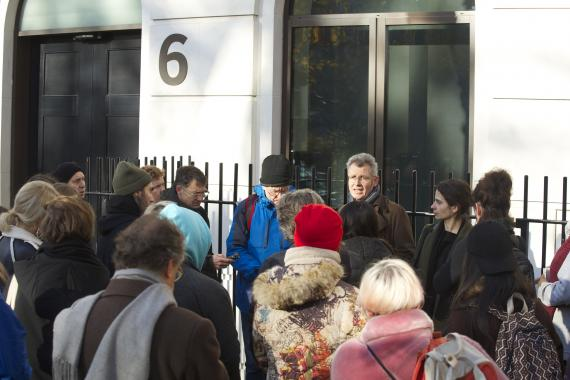 A crowd gathers around our tour guide on a London street, outside the offices of one of the largest mining companies listed on the London Stock Exchange.