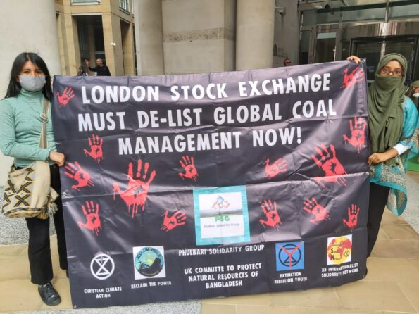 """Two people wearing face masks and green shirts hold a banner reading """"London Stock Exchange Must De-List Global Coal Management Now!"""""""